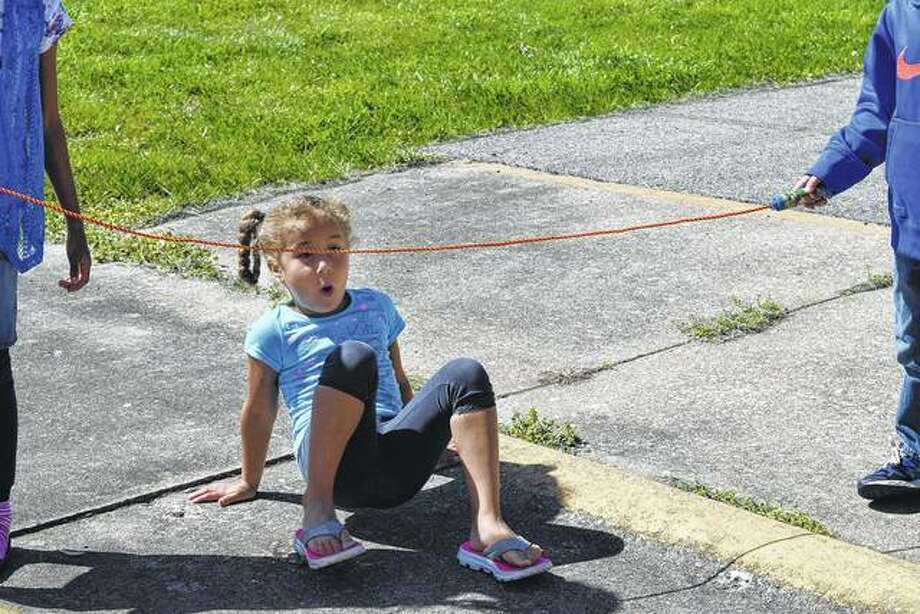 Sunshine McKenna, 5, plays a game of limbo with her friends Monday at the Bob Freesen YMCA.