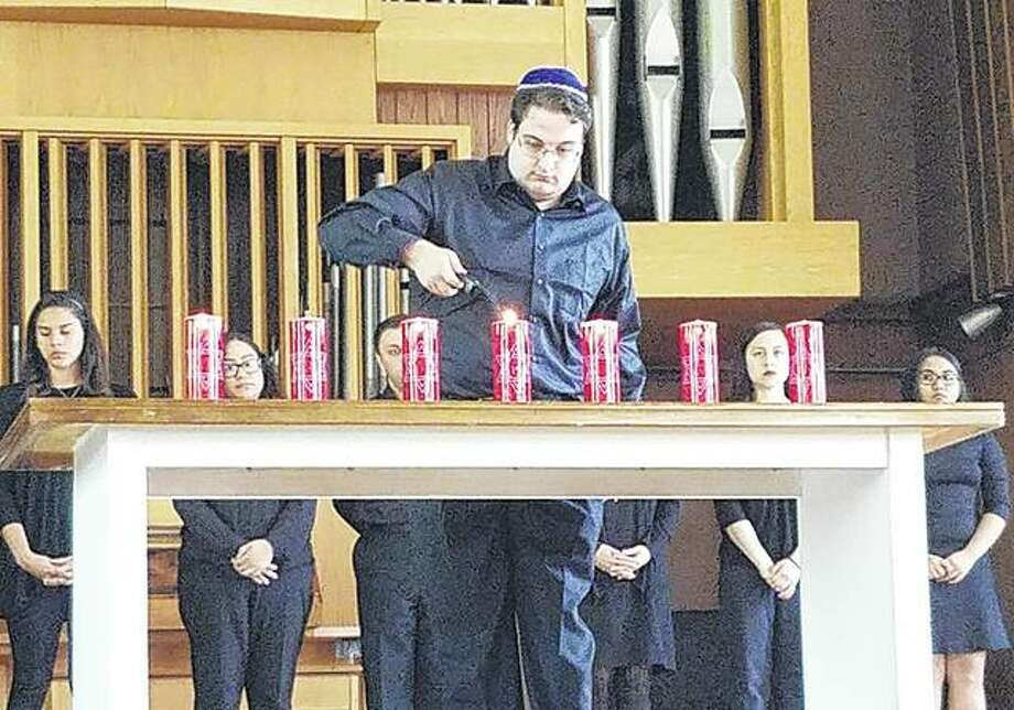 Simon Daniels lights the final candle during the Yom HaShoah convocation Monday at Illinois College. The candles represent Holocaust victims remembered and the last candle represents those undocumented. Photo: Audrey Clayton | Journal-Courier