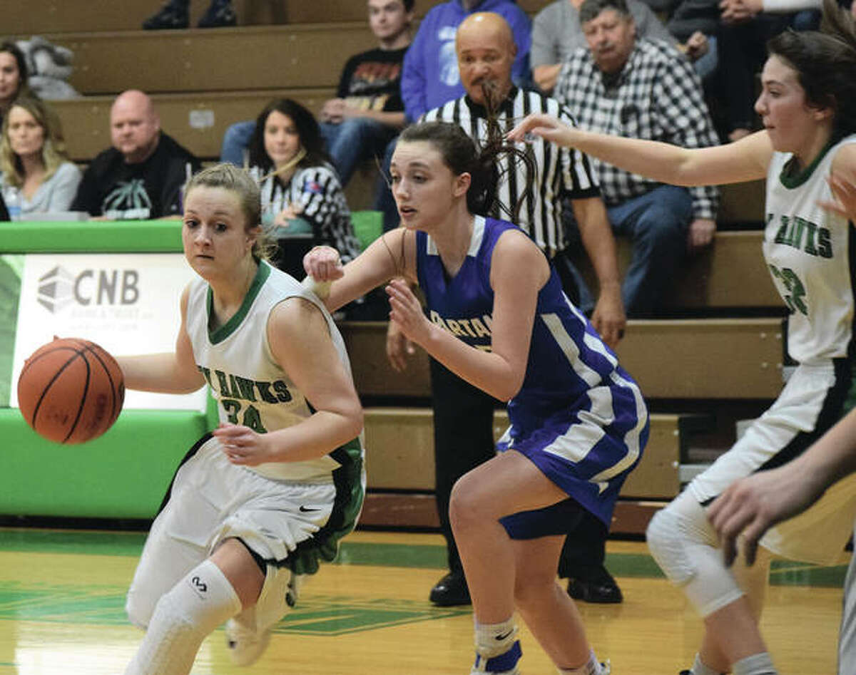 Carrollton's Hannah Krumwiede (left) drives past a North Greene defender during the Hawks' first-round victory Saturday in the 44th annual Carrollton Tournament. Krumwiede scored 31 points for the Hawks, who play Marquette Catholic in a quarterfinal Monday night.