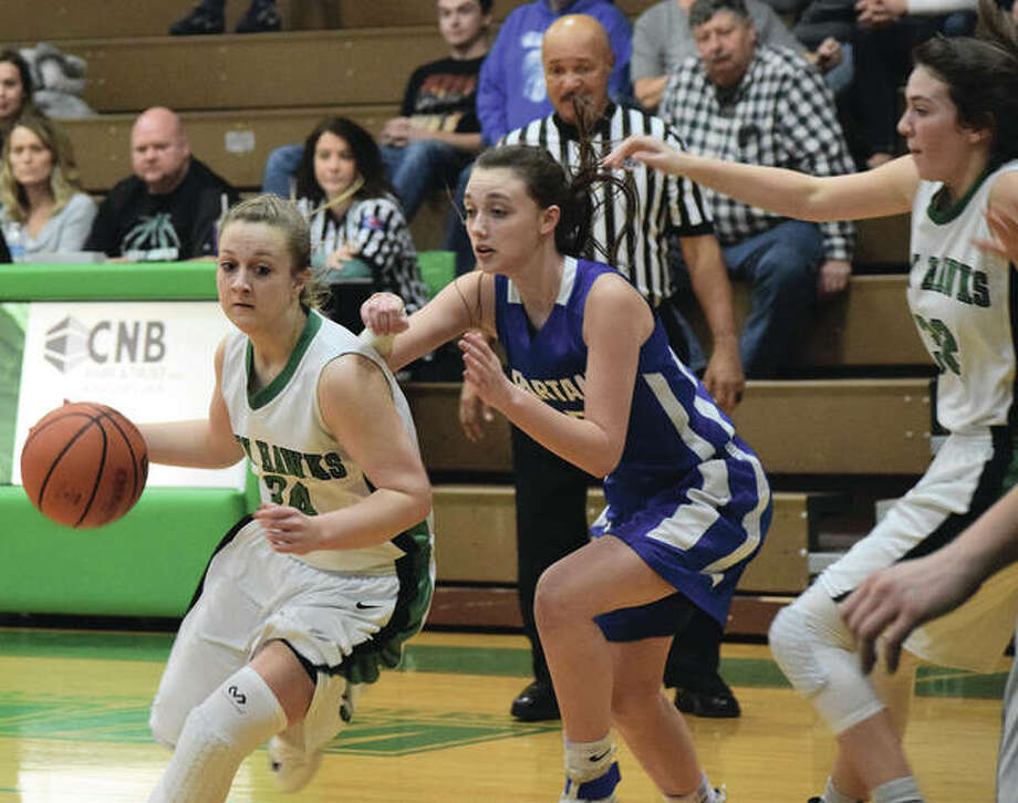 Carrollton's Hannah Krumwiede (left) drives past a North Greene defender during the Hawks' first-round victory Saturday in the 44th annual Carrollton Tournament. Krumwiede scored 31 points for the Hawks, who play Marquette Catholic in a quarterfinal Monday night. Photo: For The Telegraph