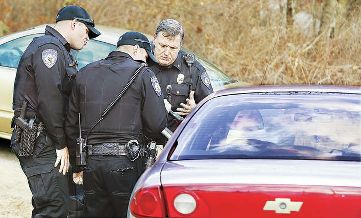 Alton Police Deputy Police Chief Terry Buhs, right, talks with officers at the door of the Chevrolet Cavalier the woman was driving when she was apparently shot.