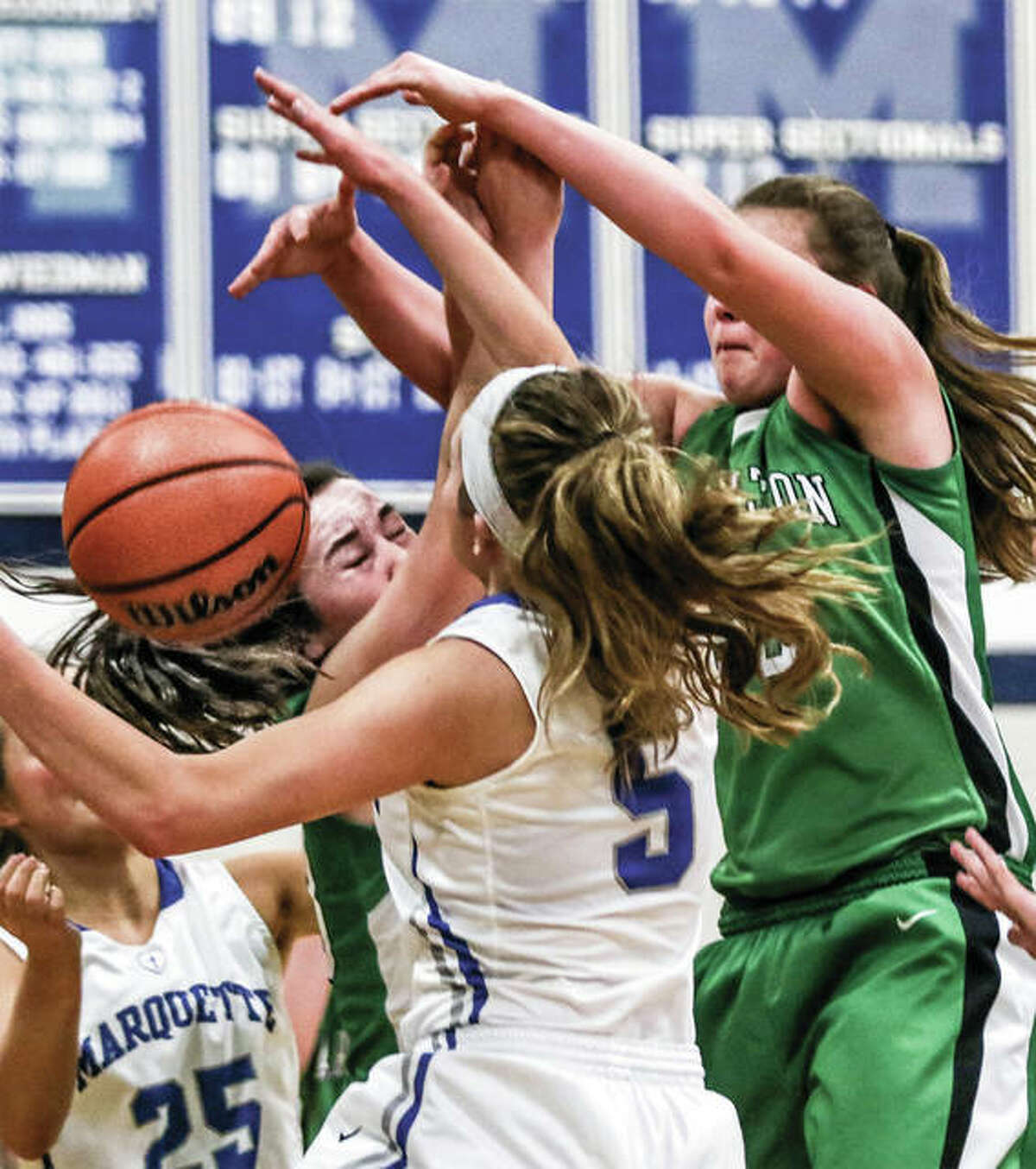Marquette Catholic's Lila Snider (5), Payton Connors (25) join Carrolton's Ava Uhles and Claire Williams (right) in a scrum for a rebound in a Jan. 2 game in Alton. The Explorers and Hawks met again Monday night at the Carrollton Tourney.