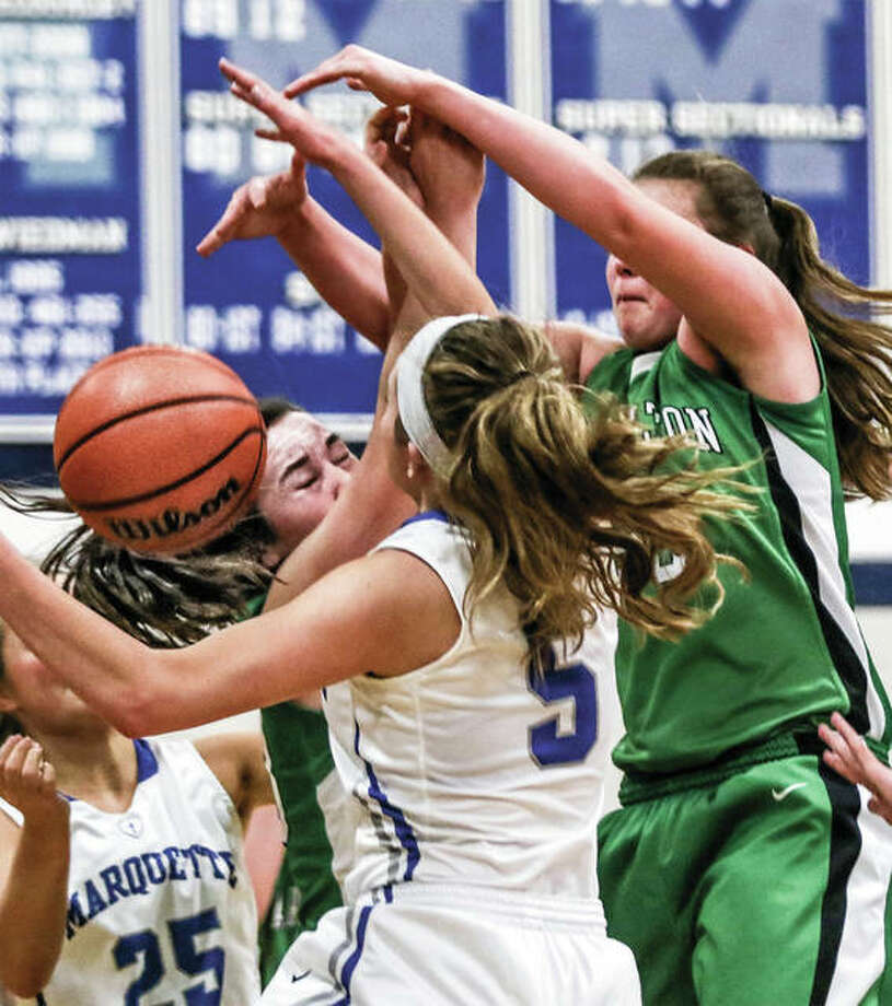 Marquette Catholic's Lila Snider (5), Payton Connors (25) join Carrolton's Ava Uhles and Claire Williams (right) in a scrum for a rebound in a Jan. 2 game in Alton. The Explorers and Hawks met again Monday night at the Carrollton Tourney. Photo: Nathan Woodside / For The Telegraph