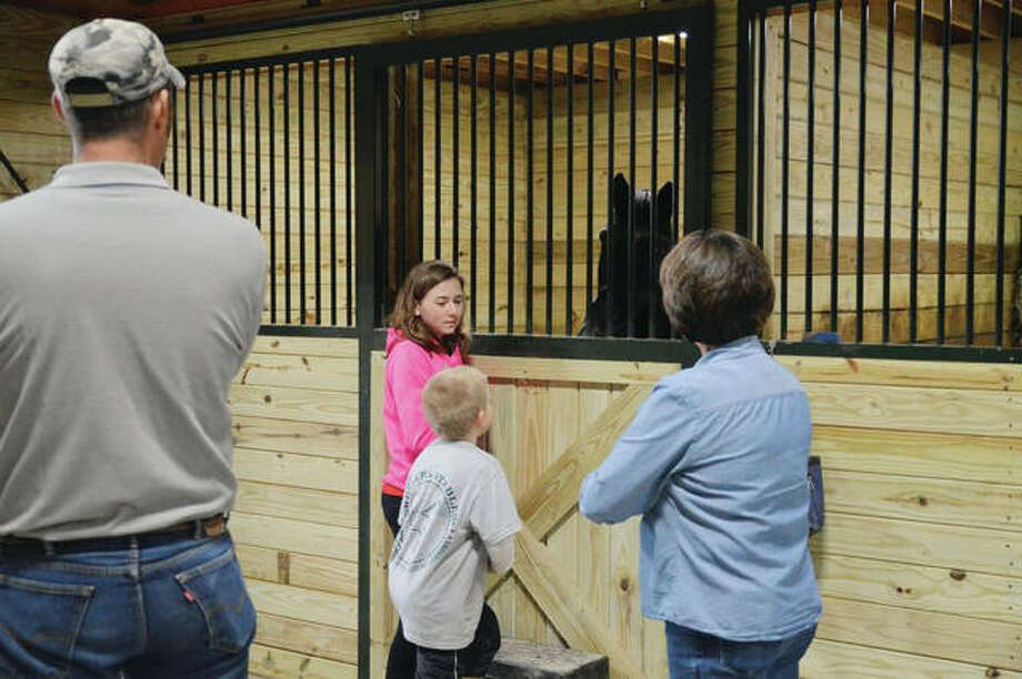 Josh Wohler (left) listens Sunday as Taylor Turley (second from left), 13; and her mother, Debbie (right), both of Loami; talk with another visitor during a barn opening for Wohlers Stables in rural Waverly. Josh Wohler and his wife, Tiffany, have opened the stables to offer a range of equine services. Photo: Kathleen Clark | For The Journal-Courier
