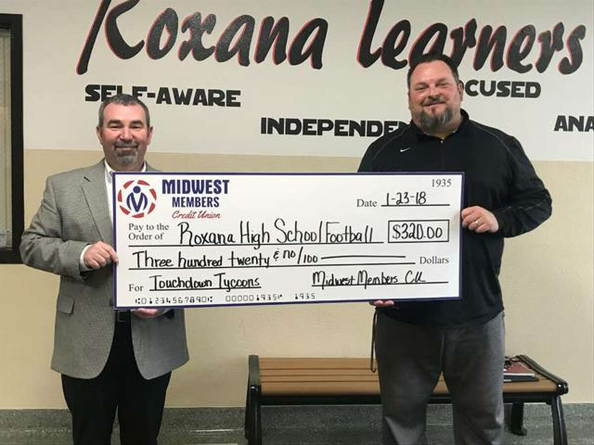 From left, Lou Bicanic, executive vice president of Midwest Members Credit Union, presents a $320 check to Pat Keith, Roxana High School head football coach.