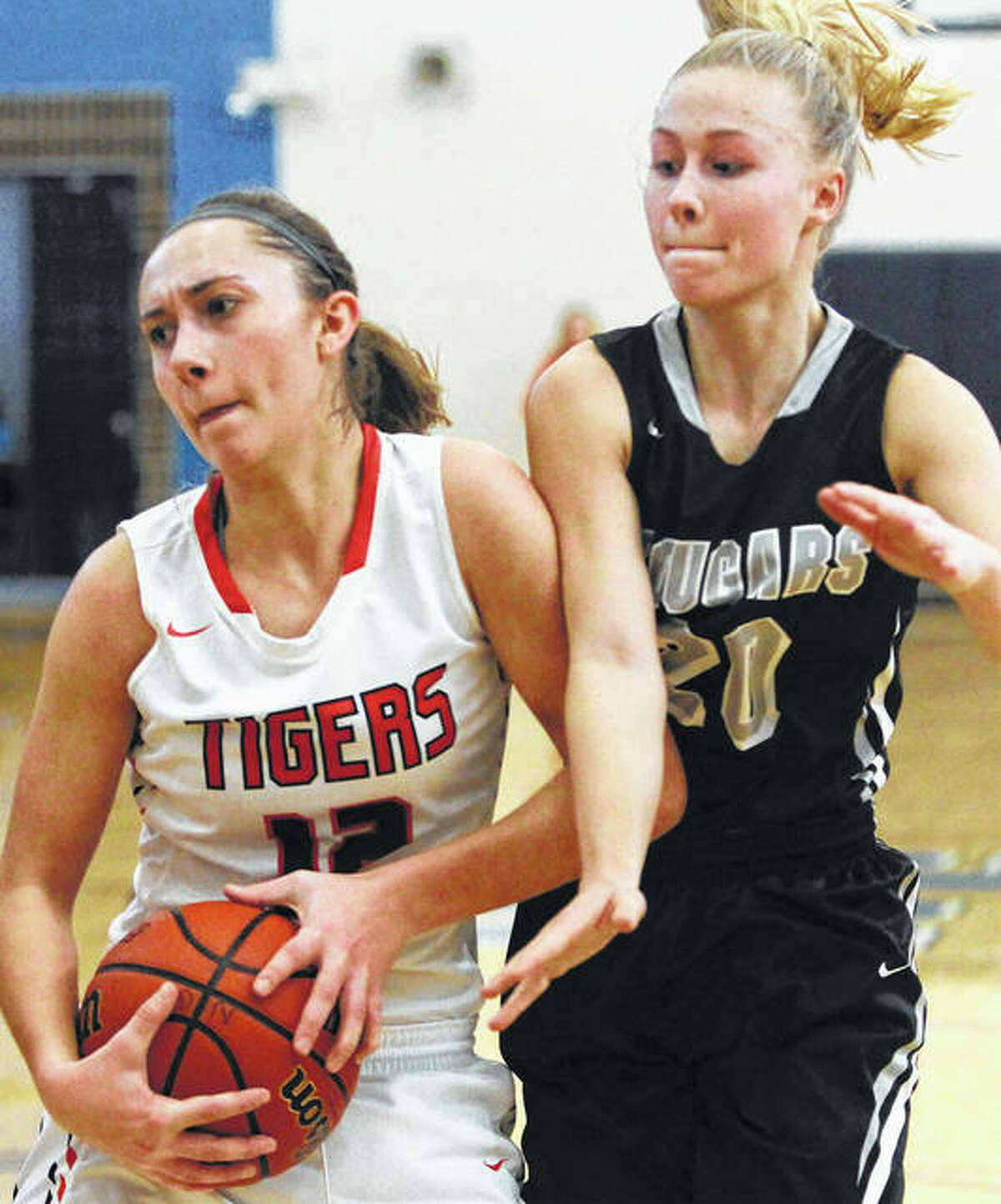 Greenfield's senior Kassidy Walters (left) secures a rebound as Winchester West Central's Maddie Lashmett tries to knock the ball away during the third-place game of the North Greene Tournament on Jan. 13 in White Hall. Back in tourney action Wednesday night at Carrollton, Walters scored 23 points in a Tigers' win to become Greenfield's all-time leading scorer with 1,590 career points.