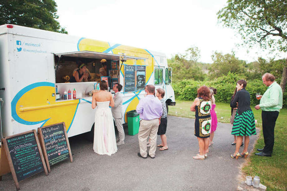 Jay and Erin Gaskill lead the line as they and their wedding guests order food from Boston-based food truck, Mei Mei, at their wedding in Sagamore Beach, Massachusetts. Couples looking for a more casual option to a sit-down dinner reception after their wedding are more frequently steering toward food trucks. Photo: Katherine Harper | Ava Marie Photography | AP