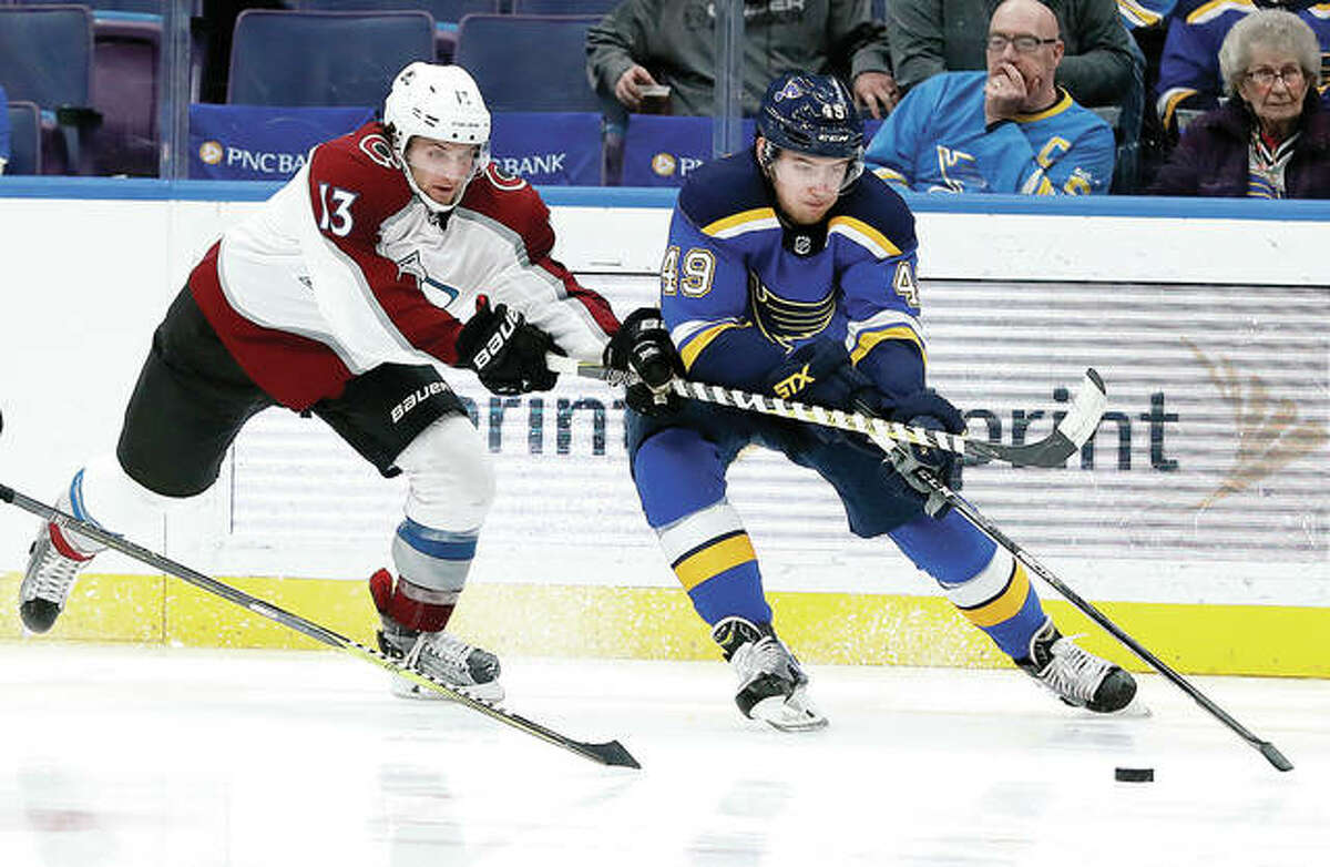 Colorado's Alexander Kerfoot, left, forechecks the Blues' Ivan Barbashev during Thursday night's game in St. Louis.