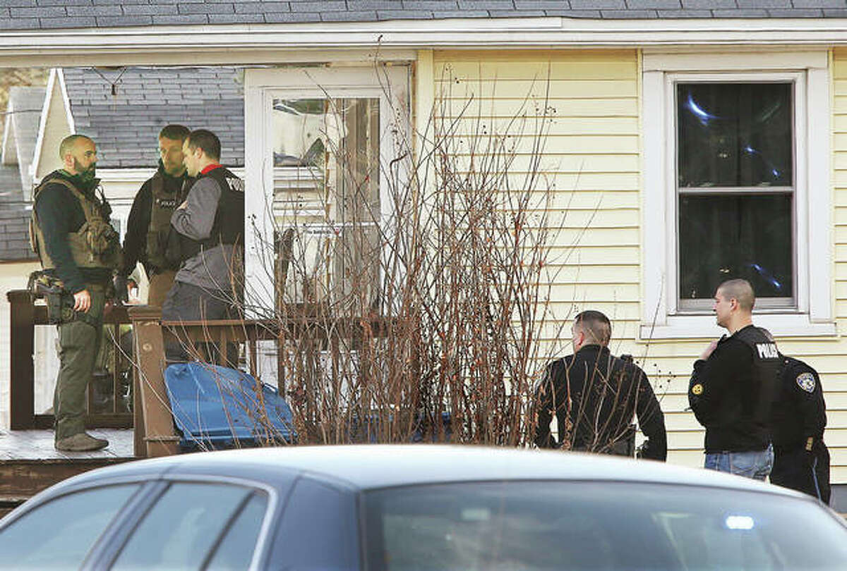 U.S. Marshals, left, and Alton police, right, stand outside a house Friday morning in the 3500 block of Omega Street, where a 42-year-old man was shot and killed during a warrant arrest. Madison County deputy coroners were called to the scene, and the street was being blocked by Alton police for a block in each direction. Alton police were apparently not initially involved in the operation until shots were reported being fired.