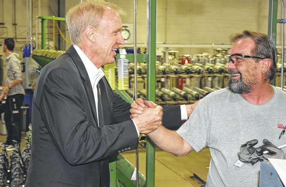 Gov. Bruce Rauner meets an employee at ILMO Products Co. during a visit to the Jacksonville business Tuesday.