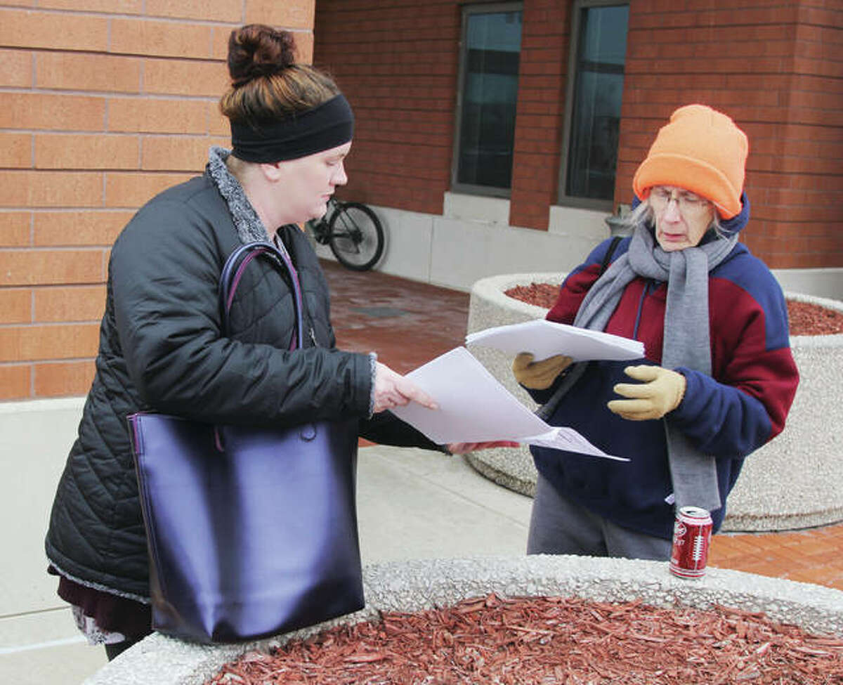 Brittany Pinnon , left, hands out forms to first-time volunteer Diane Martin for for the annual homeless count last year. The group met in front of the Donald E. Sandidge Alton Law Enforcement Center before fanning out. This year's count is set for Monday.