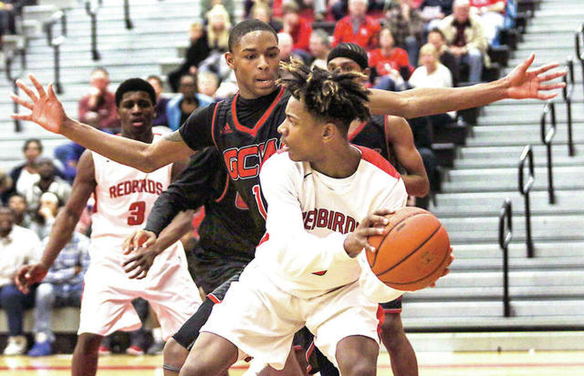 Alton's Moory Woods looks for space while being guarded by Granite City's Emmit Gordon during Southwestern Conference basketball action Friday night at Alton High School.