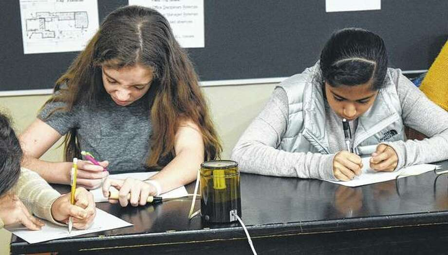 Turner Junior High School eighth-graders Megan Walker (left) and Esha Kulkarni participate in a practice Scholastic Bowl match Thursday before the team travels to Peoria today to compete in the state championship. Photo: Samantha McDaniel-Ogletree | Journal-Courier