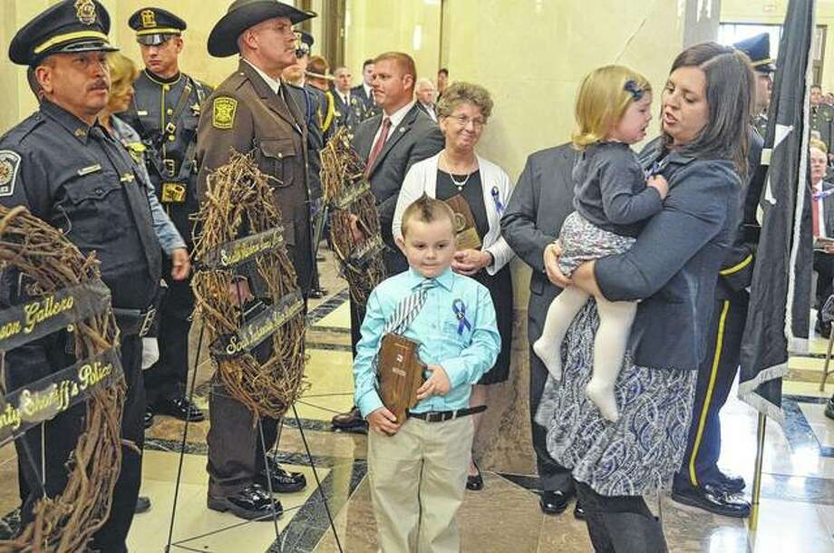 "Five-year-old Colton Fitzgerald holds a plaque honoring his father, South Jacksonville Patrolman Francis ""Scot"" Fitzgerald. The officer died in March 2016 of injuries suffered when his patrol car and an ambulance collided while in route to a medical call. Photo: David Blanchette 