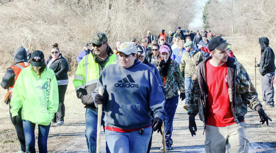 Dozens of volunteers trek to the remote, wooded area where missing Alton woman Adria Hatten's abandoned vehicle was found earlier this week. Photo: Nathan Woodside | For The Telegraph