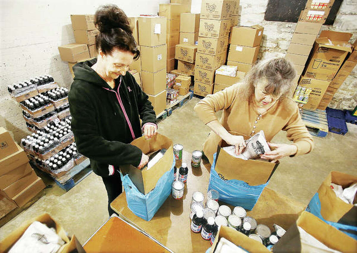 Riverbend Community Food Pantry's new interim director, Julia Shaw-Duncan, left; and chairperson of the pantry's board of directors, Nancy Hultz, right, recently packed bags of food at the pantry at 929 Milnor St., in Alton.