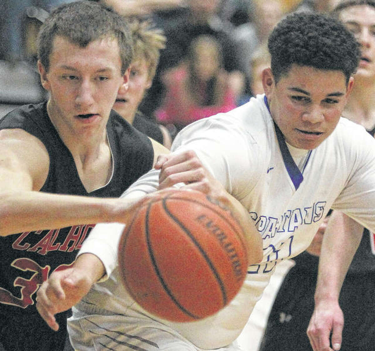 North Greene's Zion Thomas (right) and Calhoun's Corey Nelson go after a rebound during Saturday night's championship at the Beardstown Tournament. North Greene won 52-49.