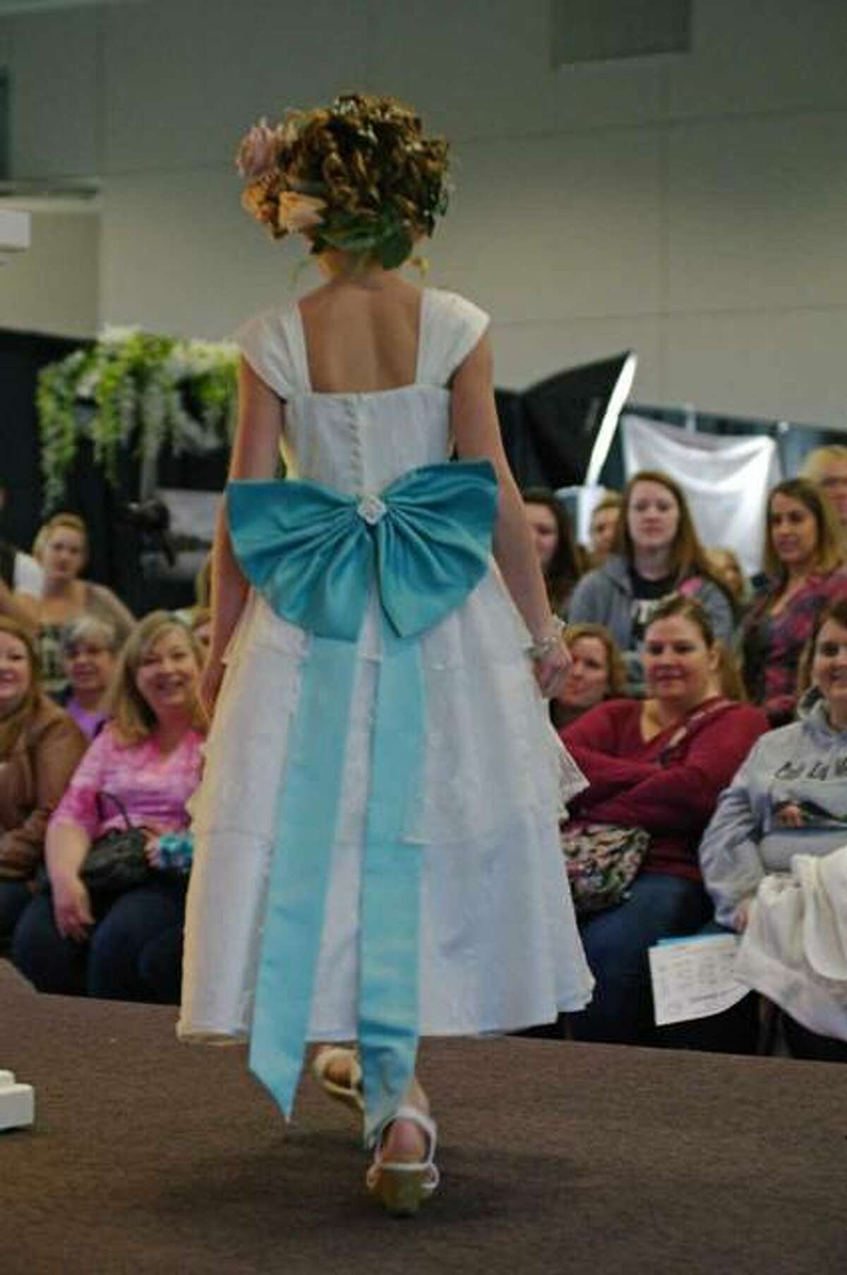 A flower girl dress being modeled at the bridal fashion show.