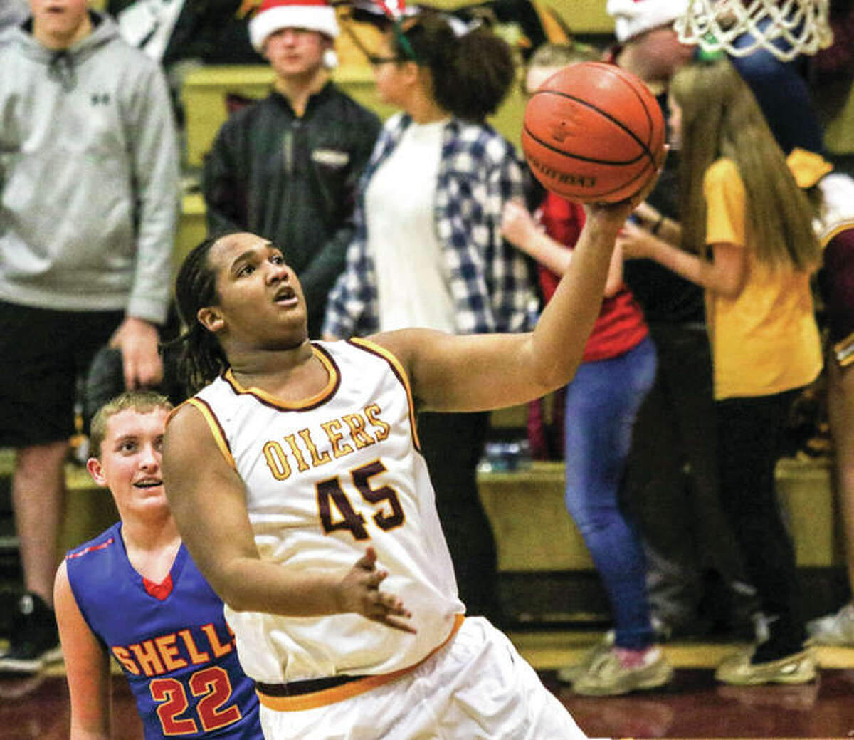 EA-WR's Darren Spruill (45) goes in for a layup as Roxana's Jacob Golenor watches the play during a game between the rivals on Dec. 8 at Memorial Gym in Wood River. The Oilers won that game vs. Roxana, but the Shells won a rematch Jan. 19 at the Litchfield Tournament.
