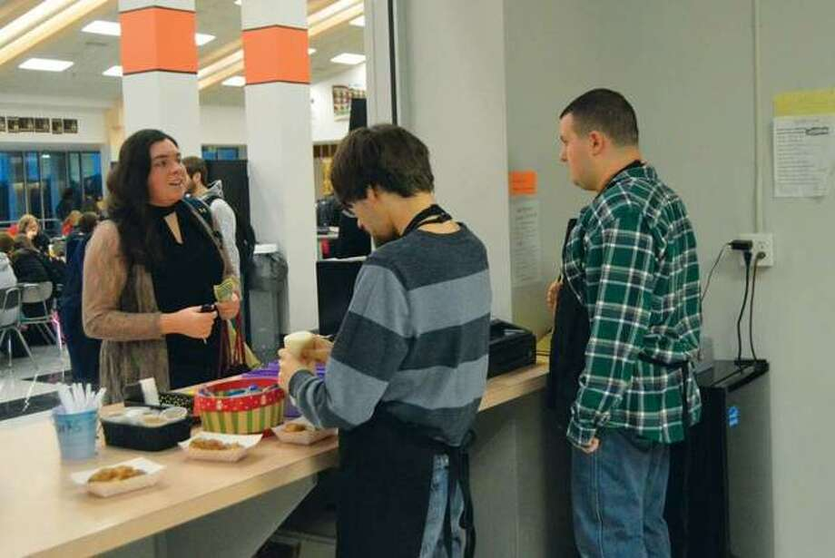 Edwardsville High School student Sydney Sahuri makes a purchase at the Tiger Den before the start of school. FLS students Caleb Byrd, left, and Cameron Ellsworth are behind the counter. Photo: Matthew Kamp | For The Telegraph