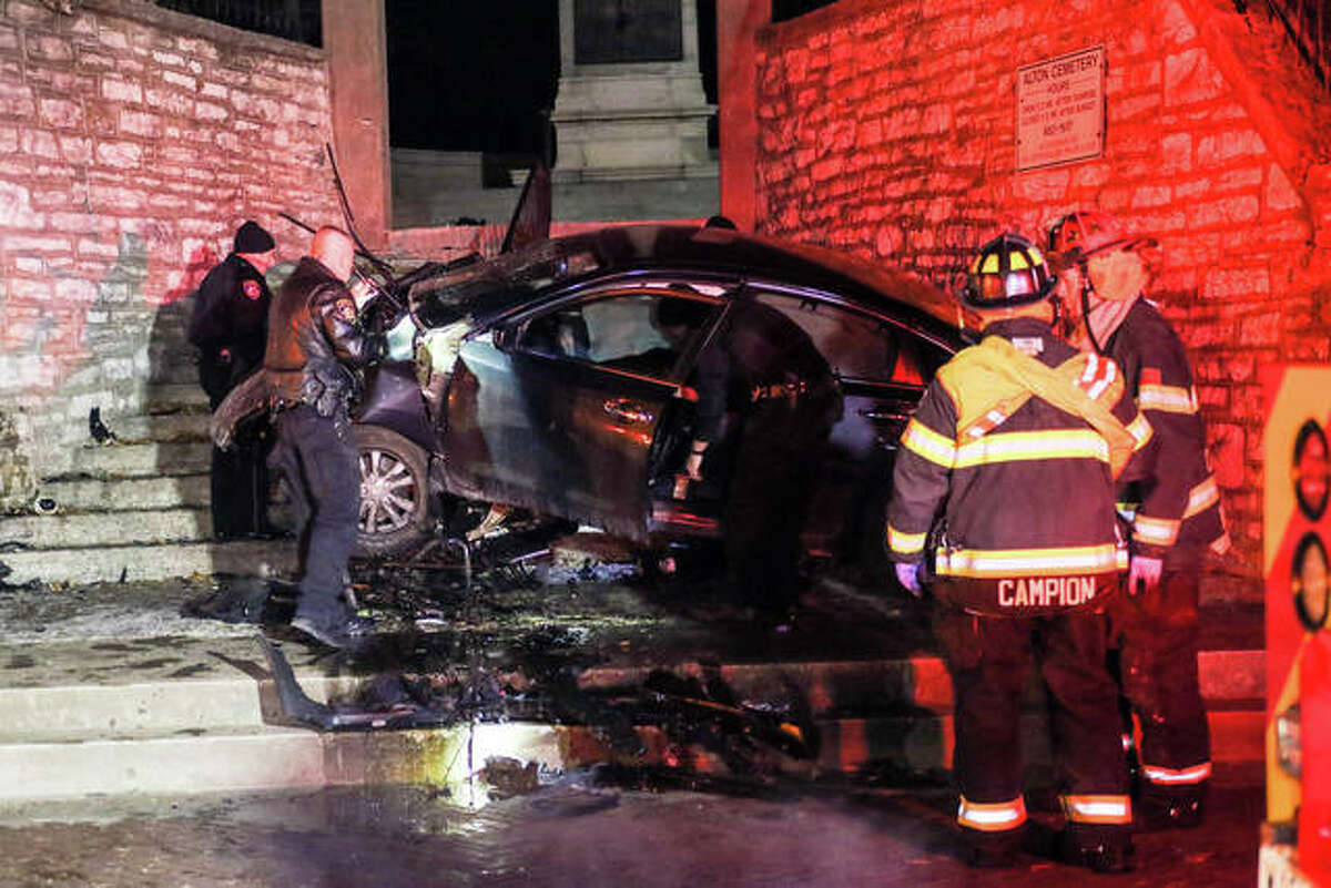 Alton police and fire personnel respond early Monday to a car that crashed into the steps leading up to the Lovejoy Monument in Alton Cemetery.