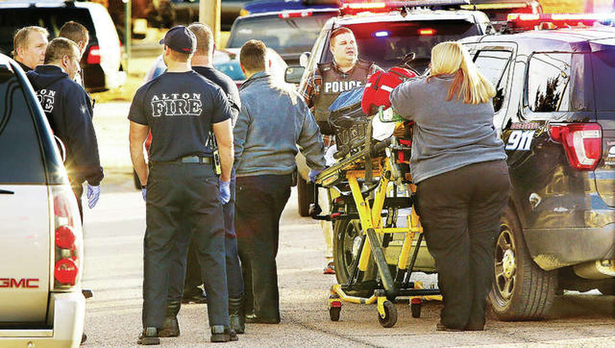 Alton police, firefighters and paramedics from Alton Memorial Ambulance service take cover behind police cars Friday, waiting for the all clear to enter the residence to check on the condition of a man who had been shot. The man was identified by the Madison County Coroner's Office Monday as Matthew W. Zimmerman of Alton.