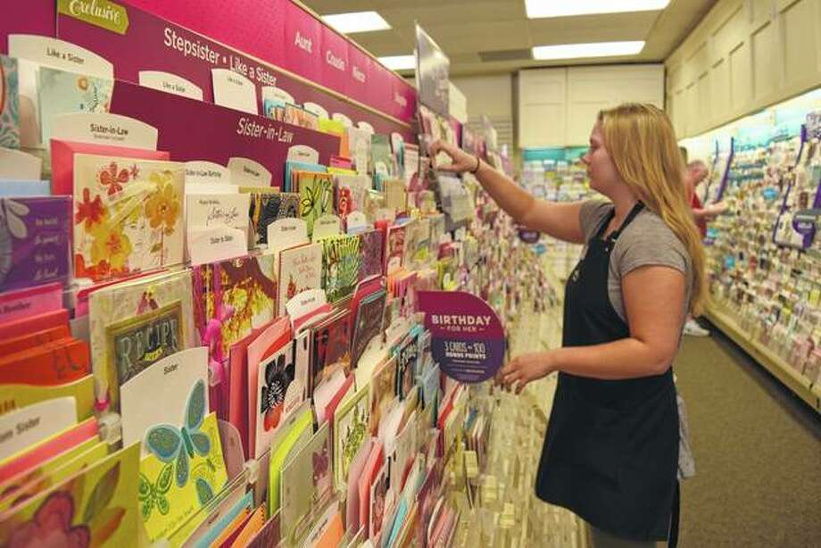 Kirlin's sales associate Kayla Godair of Woodson moves greeting cards around on a display rack at the Lincoln Square Shopping Center store, which will close June 25. Photo: Greg Olson | Journal-Courier