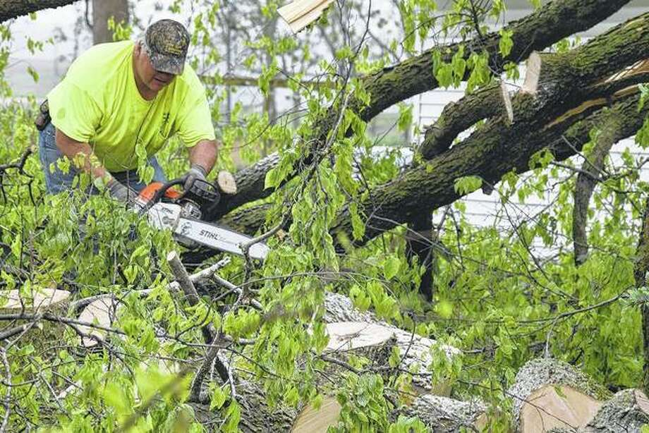 A unidentified Concord resident uses a chainsaw Thursday to cut tree limbs that were knocked to the ground by a storm system that brought high winds through the town the night before. Photo: Samantha McDaniel-Ogletree | Journal-Courier