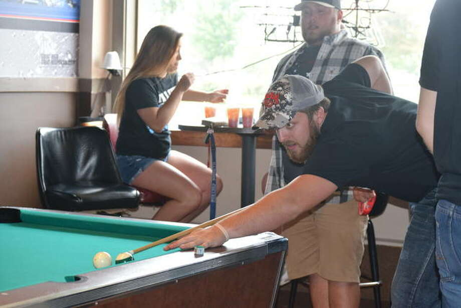 Illinois College student Fischer Tharp aims for the winning shot in his pool game Thursday at On The Rox in Jacksonville. Photo: Audrey Clayton | Journal-Courier