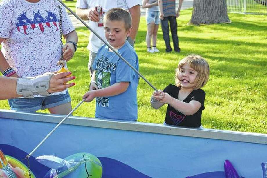 Jayden Williams (left), 9, and Baylee Williams, 3, the children of James Williams and Michelle Evans of Jacksonville, play a game Friday at the carnival in Community Park. The carnival will be open again today from 10 a.m. to 10 p.m. Photo: Samantha McDaniel-Ogletree | Journal-Courier