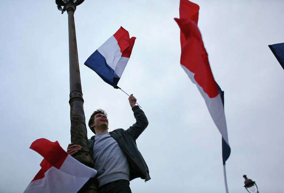 Thibault Camus | AP A supporter of French independent centrist presidential candidate Emmanuel Macron celebrates outside the Louvre museum in Paris, France.