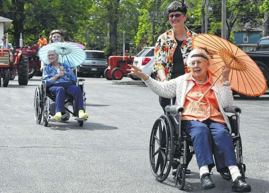 "Jean Cornelius, 100, and Catherine DeFrates, 101, lead the third annual ""personal parade"" Monday at Heritage Health. The parade featured a fire truck from the Jacksonville Fire Department, antique cars and tractors and a performance by the Jacksonville High School Drumline."