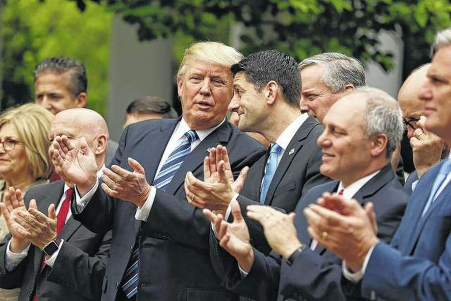 President Donald Trump, flanked by House Ways and Means Committee Chairman Rep. Kevin Brady, R-Texas, and House Speaker Paul Ryan of Wisconsin, are seen in the Rose Garden of the White House in Washington on May 4 after the House pushed through a healthcare bill.