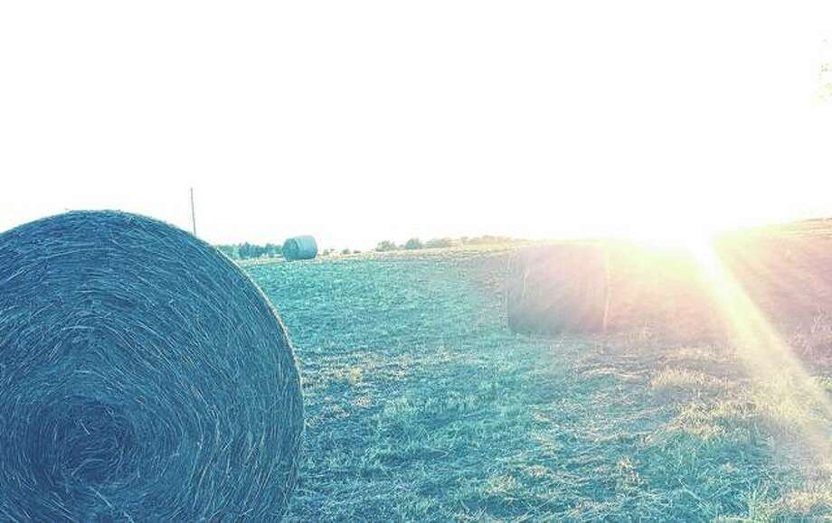 The sun sets over a field dotted with hay bales. Photo: Joy Harris | Reader Photo
