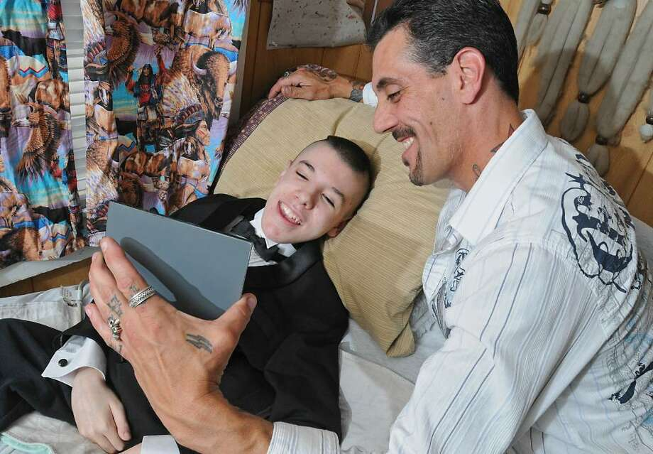 Shawn Zielinski holds up a mirror for his 18-year-old son Tylar Zielinski to see how he looks in a tuxedo, the day befoer his May 15 prom at Fonda-Fultonville High School. (Lori Van Buren / Times Union) Photo: LORI VAN BUREN