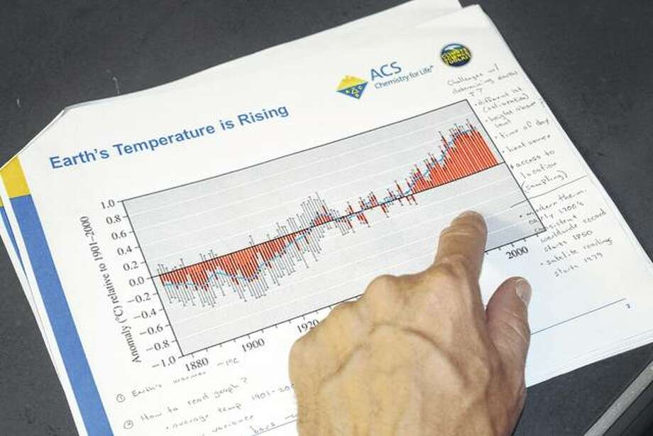 Illinois College chemistry professor Brent Chandler points to a graph showing how much Earth's temperature has risen since 1880. Chandler gave a presentation on climate change Saturday at The Soap Co. Coffee House on the east side of the Jacksonville square. Photo: Greg Olson   Journal-Courier