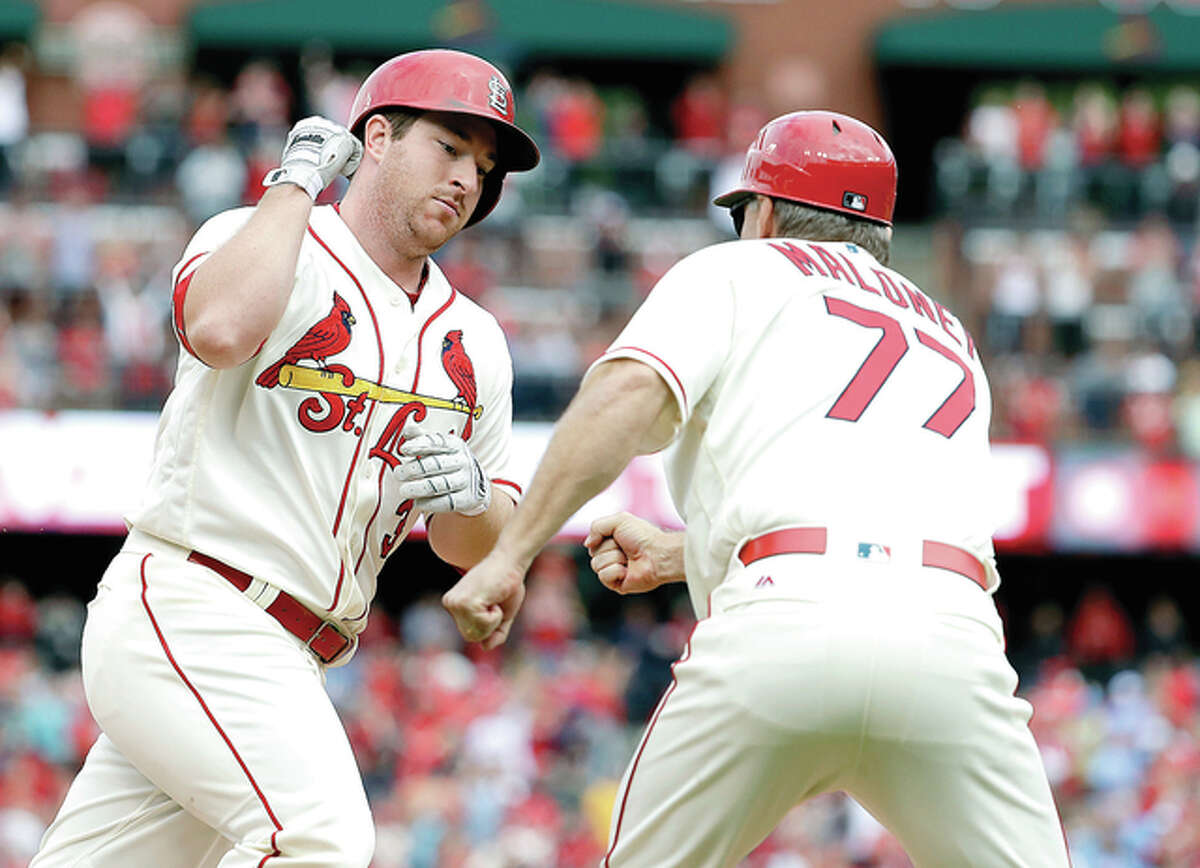 The Cardinals' Jedd Gyorko, left, is congratulated by third base coach Chris Maloney while rounding the bases after hitting a solo home run in the eighth inning of Saturday's win over the Pirates at Busch Stadium.