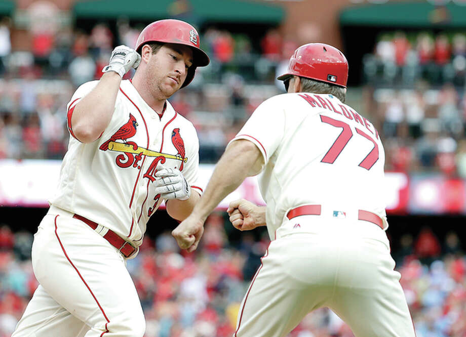 The Cardinals' Jedd Gyorko, left, is congratulated by third base coach Chris Maloney while rounding the bases after hitting a solo home run in the eighth inning of Saturday's win over the Pirates at Busch Stadium. Photo: AP