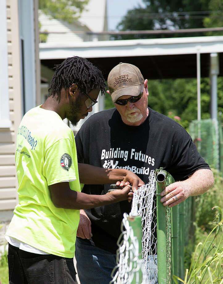 Andre Ewing works on the installation of a new fence with YouthBuild Construction Trainer Mitch Fletcher, as a part of the program's 2016 Central Avenue Beautification project.