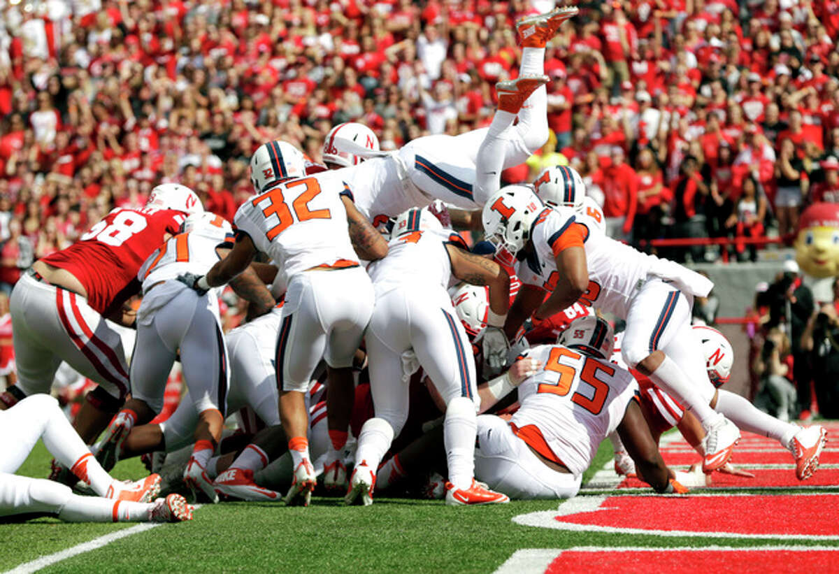 Nebraska quarterback Tommy Armstrong Jr. is buried under a pile of players as he scores a touchdown against Illinois Saturday in Lincoln, Neb.