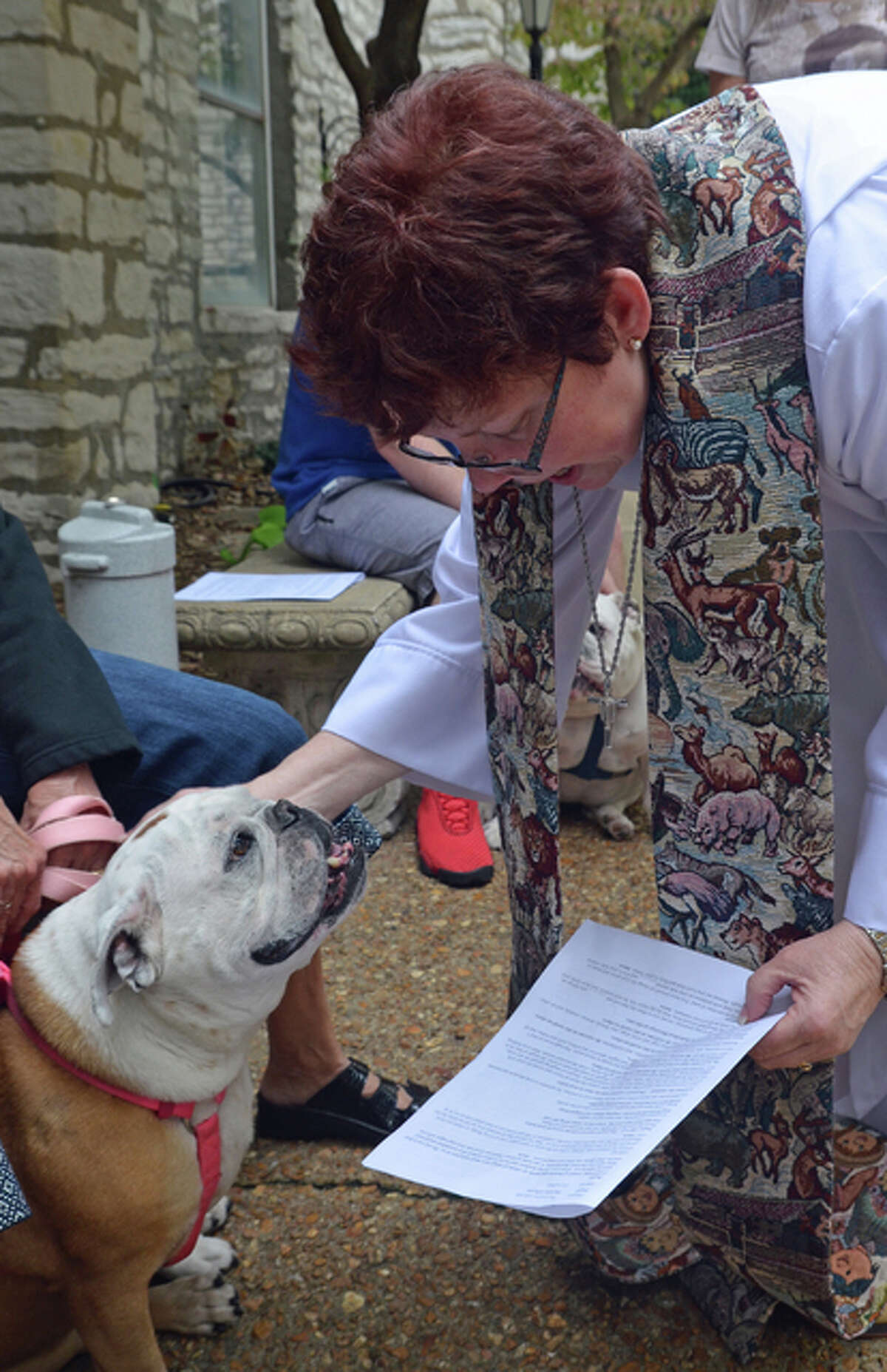 Maggie the bulldog receives a blessing Sunday afternoon from rector Cynthia Sever during the annual Blessing of the Animals service at the Episcopal Parish of Alton located Downtown.