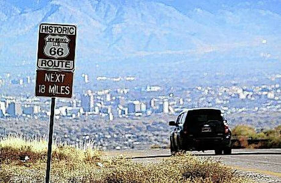 Susan Montoya Bryan | AP A car travels down historic Route 66 toward Albuquerque, New Mexico. Route 66, the historic American road that linked Chicago to the West Coast, soon may be dropped from a National Park Service preservation program.