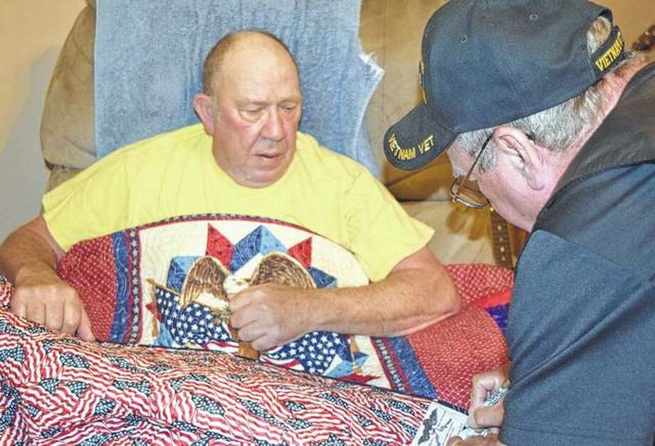Army veteran Gerald VanHyning (seated) watches Tuesday as Randall Hester of the Quilt of Valor Foundation puts the finishing touches on a quilt awarded to VanHyning for his service.