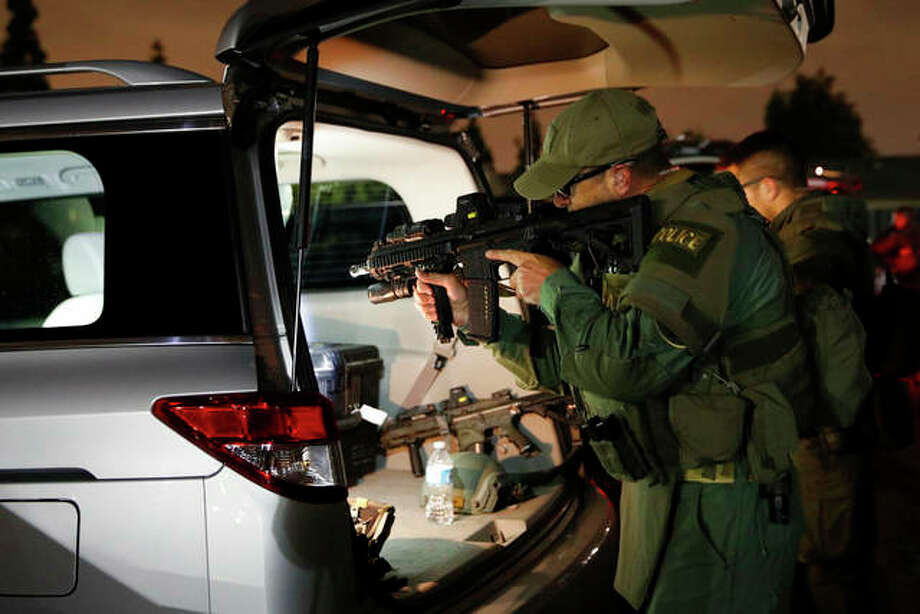 Jae C. Hong | AP An ATF agent checks his weapon as he gets ready for a raid May 17 in Los Angeles. Hundreds of law enforcement fanned out across Los Angeles, serving arrest and search warrants as part of a three-year investigation into the violent and brutal street gang MS-13.