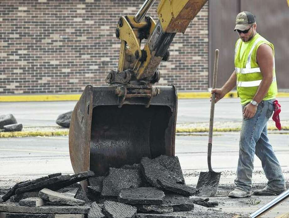 Brad Ford of Versailles, an employee of United Contractors Midwest, watches as the approach to Morton Avenue from the Lincoln Square Shopping Center is broken up Wednesday in preparation for a phase of an ongoing road project.