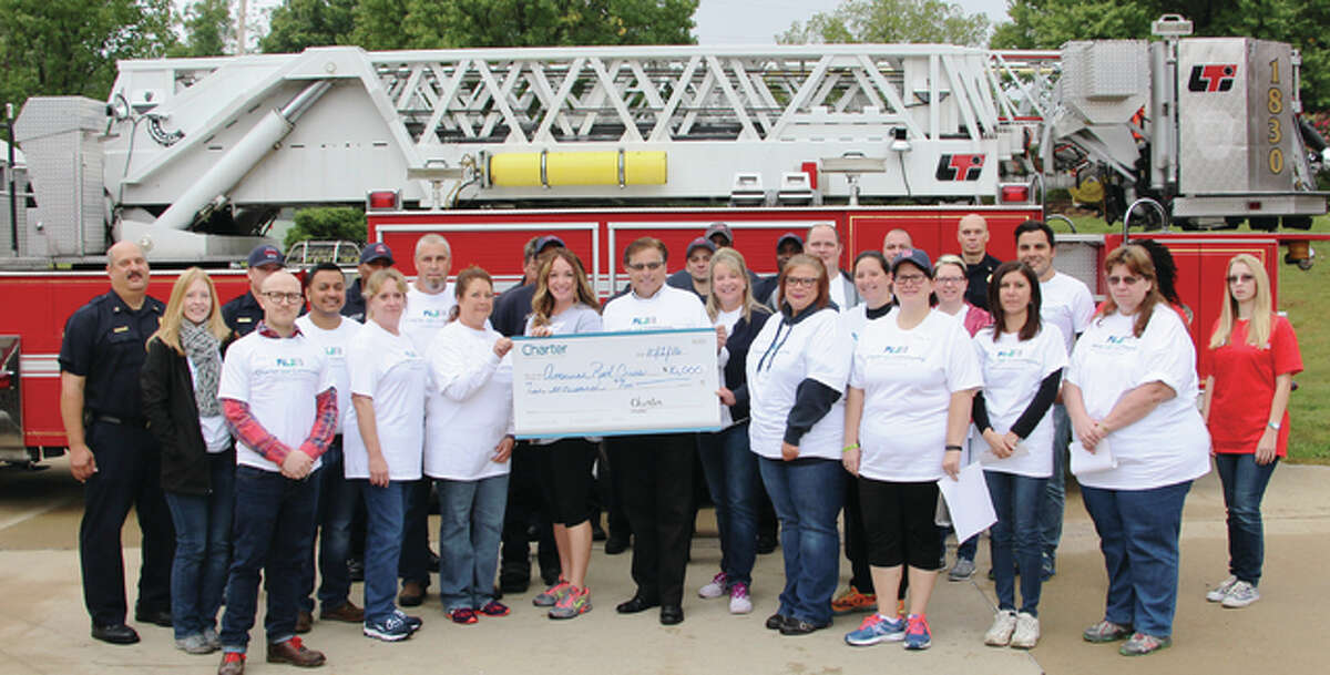 Charter Communications presents a check for $10,000 to the Red Cross of Eastern Missouri for its fire preparedness campaign. On Saturday volunteers went out and installed 48 smoke detectors during a canvass of Alton neighborhoods.