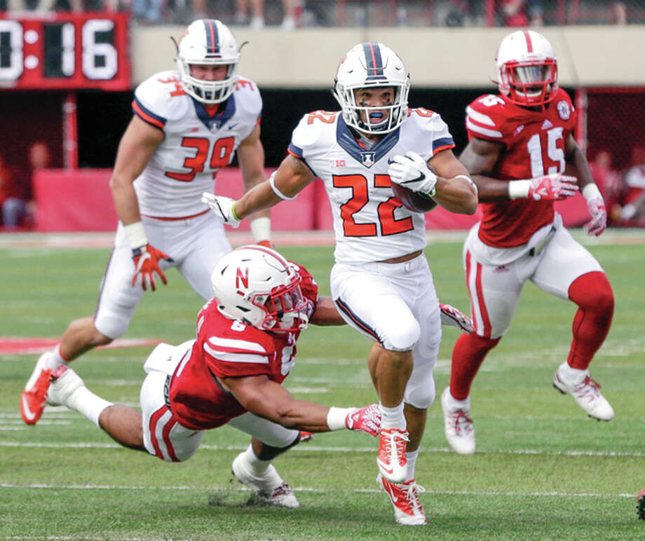 Illinois running back Kendrick Foster (22) runs for a touchdown away from a tackle attempt by Nebraska linebacker Dedrick Young II (5) and linebacker Michael Rose-Ivey (15) last Saturday in Lincoln, Nebraska.