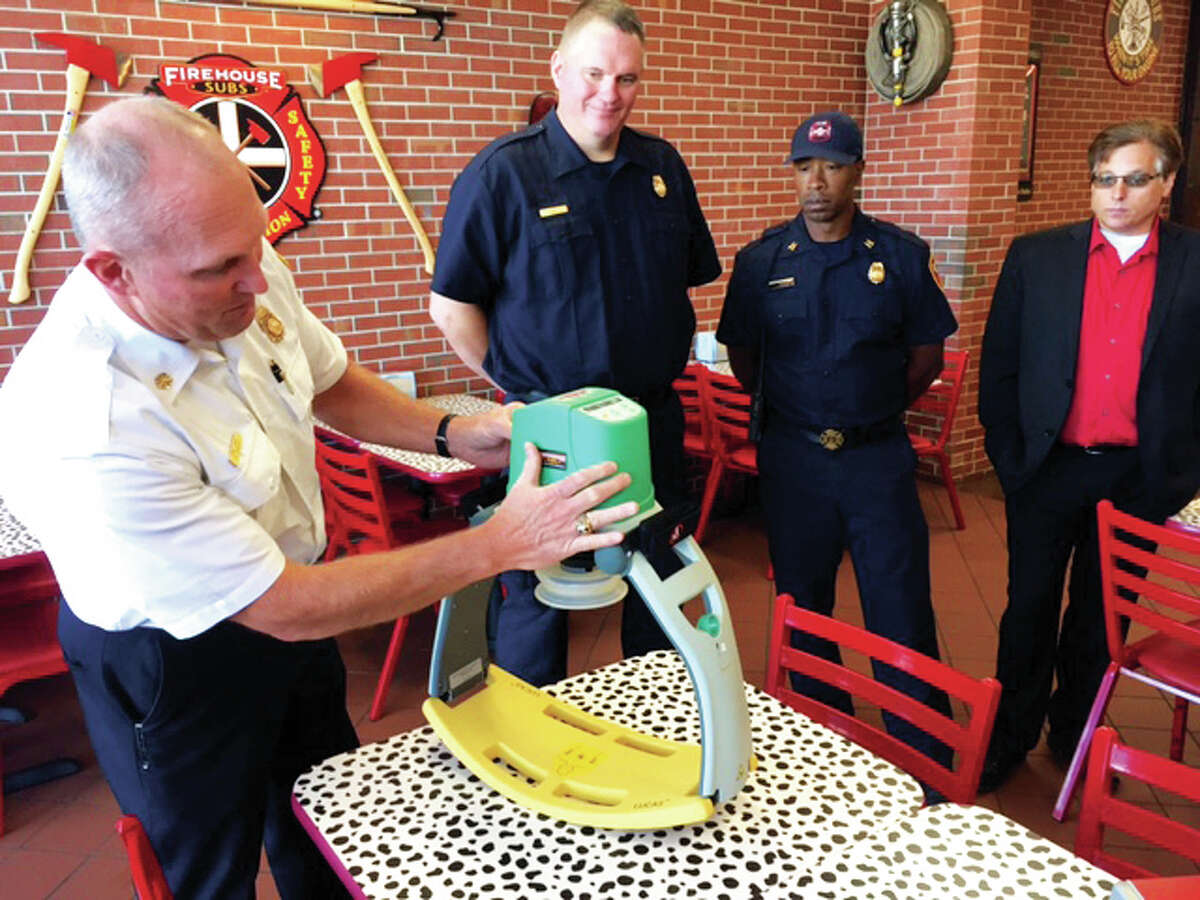 Alton Fire Department Chief Bernie Sebold explains how a new chest compression system works as department staff and Mayor Brant Walker look on. The system, worth more than $11,000, was purchased through a grant funded by Firehouse Subs donations.
