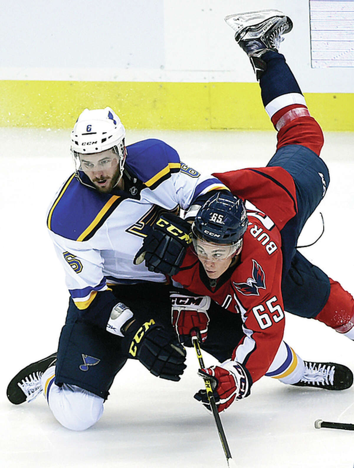 Washington Capitals left wing Andre Burakovsky (65) trips over Blues defenseman Joel Edmundson while chasing the puck in a preseason game Monday in Washington.