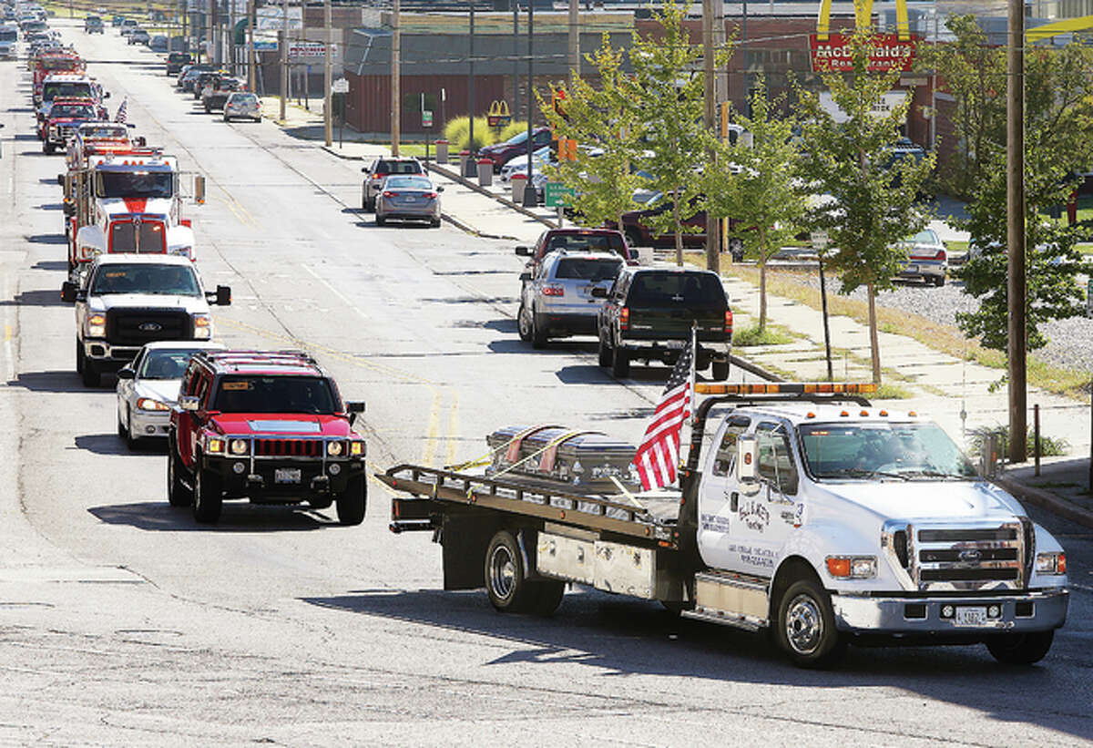 """Members of the area's towing industry gave a final - and powerful - salute to Richard """"Dick"""" Klaffer, 63, Wednesday. He was an owner of Bill and Joe's Towing in East Alton, as well as a driver. Klaffer died Sept. 30. His coffin rode on a towed flatbed trailer, followed by a dozen other towing company trucks from across the area as it made its way down East Broadway from the Elias, Kallal and Schaaf Funeral Home in Alton, on the way to burial at Scenic Hills Cemetery in Grafton. East Alton police and firefighters wore dress uniforms to honor Klaffer, a Vietnam-era U.S. Navy veteran."""